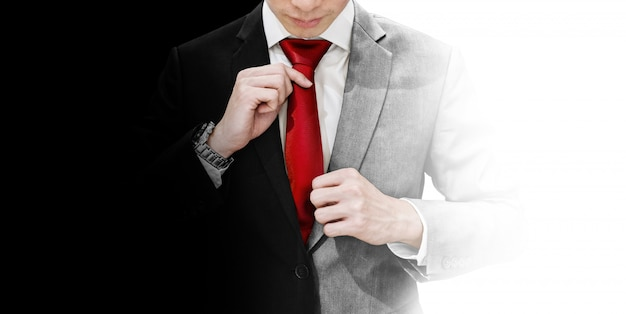 Uomo d'affari in abito bianco e nero legando cravatta rossa