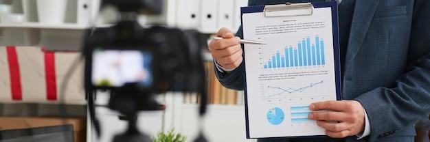 Il blogger dell'uomo d'affari dimostra ai grafici di affari della macchina fotografica con gli indicatori commerciali. corsi di sviluppo aziendale online