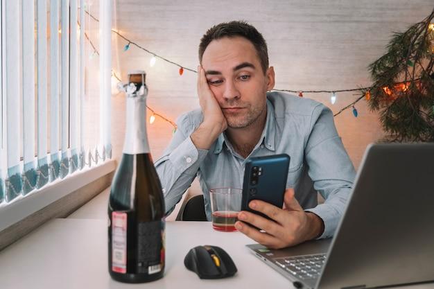 Uomo d'affari in camicia blu addormentato al lavoro con una bottiglia di alcol, ha dormito troppo a causa della festa notturna tempestosa con un drink dopo l'azienda il 1 gennaio ha celebrato il nuovo anno postumi di una sbornia molto brutta