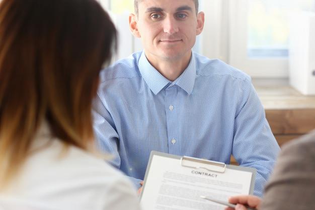 Uomo d'affari in forma di contratto di offerta della camicia blu sul cuscinetto degli appunti
