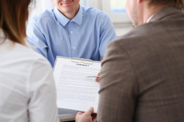Uomo d'affari in forma di contratto d'offerta della camicia blu sulla lavagna per appunti