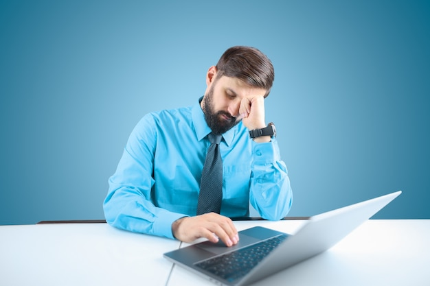 Un uomo d'affari in una camicia blu e cravatta sta lavorando pensieroso a un computer su un progetto responsabile, l'uomo si è appoggiato la mano alla testa, pensando al lavoro