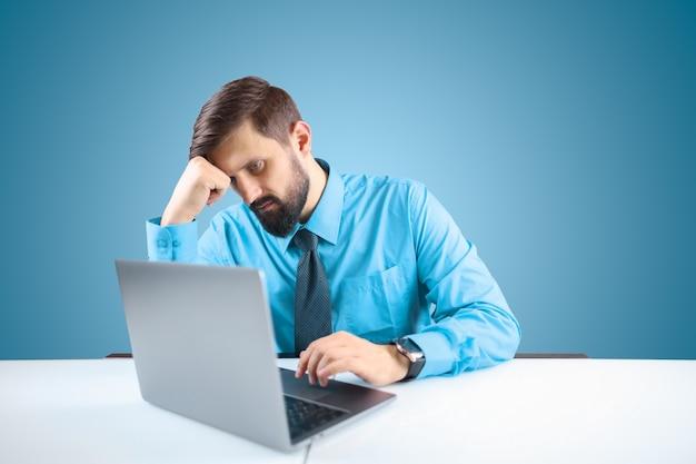 Un uomo d'affari in una camicia blu e cravatta sta lavorando minuziosamente a un computer su un progetto responsabile, l'uomo si è appoggiato la mano alla testa