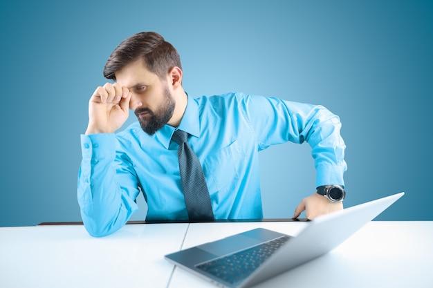 Un uomo d'affari in camicia blu e cravatta appoggia la testa sulla mano, un uomo in stile business ha mal di testa