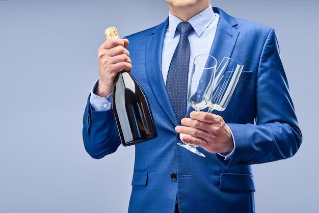 Un uomo d'affari in un abito blu detiene una bottiglia di champagne e due bicchieri