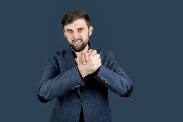 Un uomo d'affari in abito blu tiene le mani davanti a sé