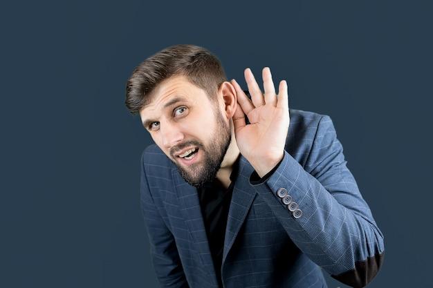 Un uomo d'affari in abito blu si mette una mano all'orecchio, cercando di sentire qualcosa.