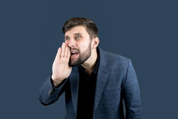 Un uomo d'affari in abito blu si mette la mano alla bocca e grida