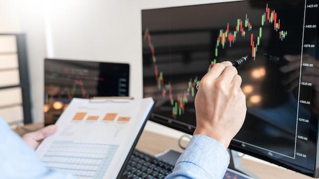 Broker di uomo d'affari analizzando grafici di dati finanziari e report sullo schermo
