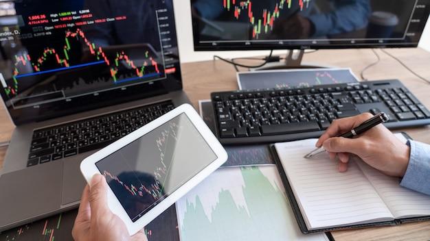 Broker dell'uomo d'affari analizzando grafici e rapporti di dati di finanza