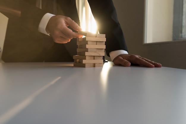 Uomo d'affari che costruisce una torre dei blocchi di legno