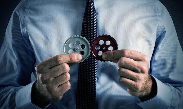 L'uomo d'affari costruisce un sistema aziendale come un meccanismo a ingranaggi