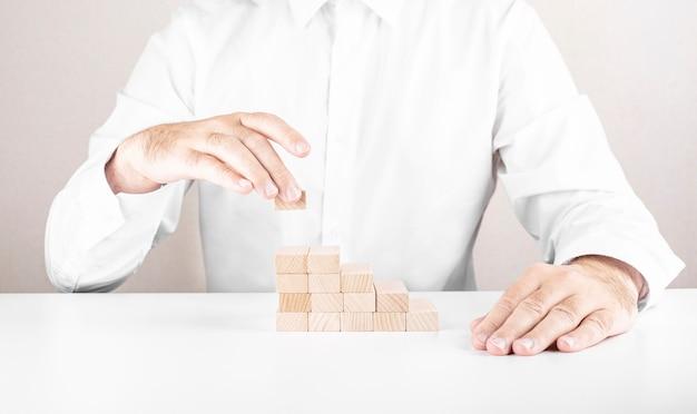 Uomo d'affari costruisce una scala da blocchi di legno concetto di crescita e successo del business