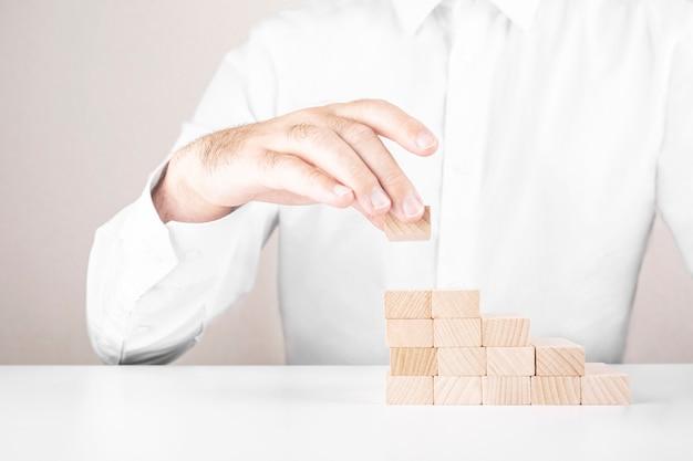 L'uomo d'affari costruisce una scala da blocchi di legno. concetto di crescita e successo del business.