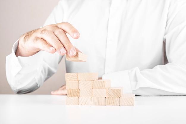 L'uomo d'affari costruisce una scala da blocchi di legno