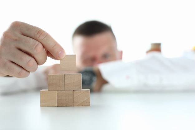 L'uomo d'affari costruisce la piramide dai cubi di legno