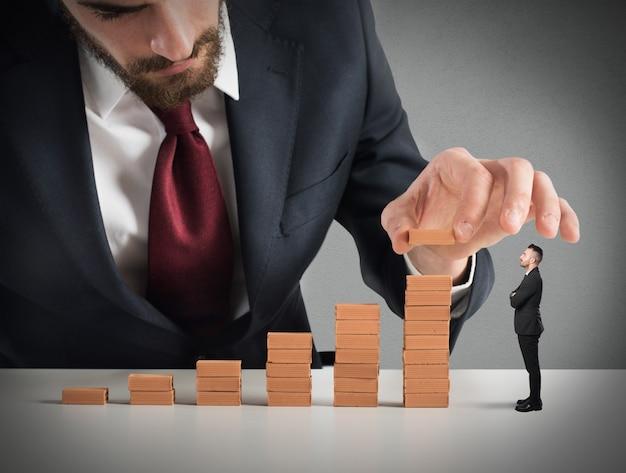 L'uomo d'affari costruisce una scala con piccoli mattoni