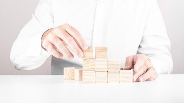 L'uomo d'affari costruisce la scala dei blocchi di legno