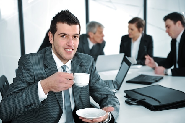 Uomo d'affari nell'ambientazione di affari che beve cofee