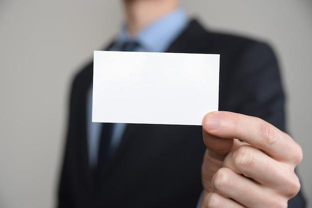 Uomo d'affari, stretta della mano dell'uomo di affari che mostra biglietto da visita - immagine ravvicinata su sfondo grigio. mostra un foglio di carta bianco. biglietto da visita cartaceo.