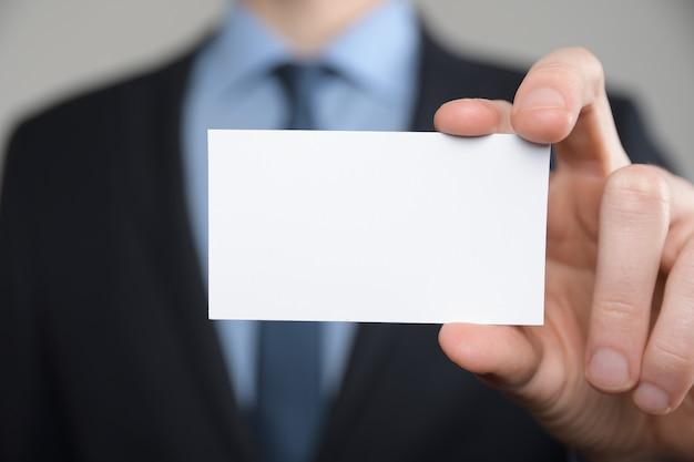Uomo d'affari, mano dell'uomo d'affari che mostra biglietto da visita - immagine ravvicinata su sfondo grigio. mostra un foglio di carta bianco. biglietto da visita cartaceo.