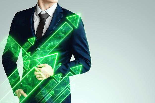 Un uomo d'affari in giacca e cravatta alla ricerca di un'opportunità sullo sfondo delle frecce verdi rivolte verso l'alto