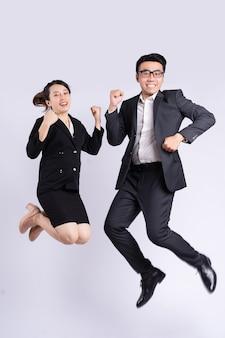 Uomo d'affari e donna d'affari che saltano su sfondo bianco