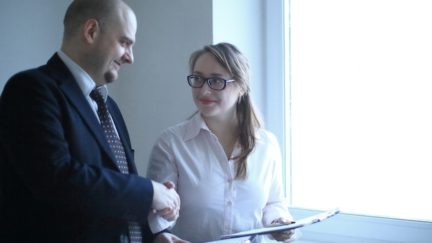 Uomo d'affari e donna d'affari che si stringono la mano in piedi vicino alla finestra.foto con copia spazio
