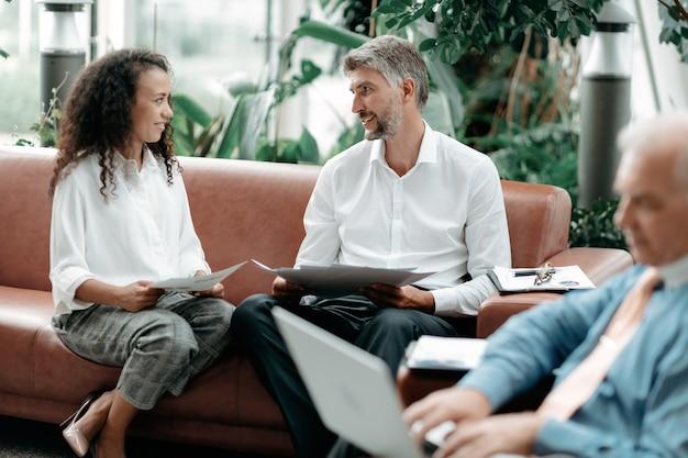Uomo d'affari e donna d'affari che discutono di documenti aziendali e finanziari