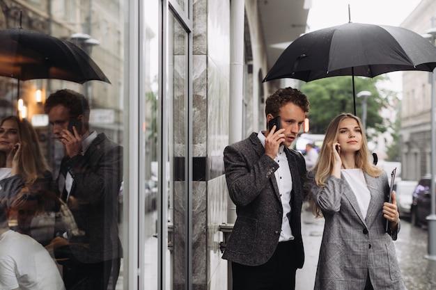 Un uomo d'affari e una donna d'affari discutendo di lavoro sotto la pioggia