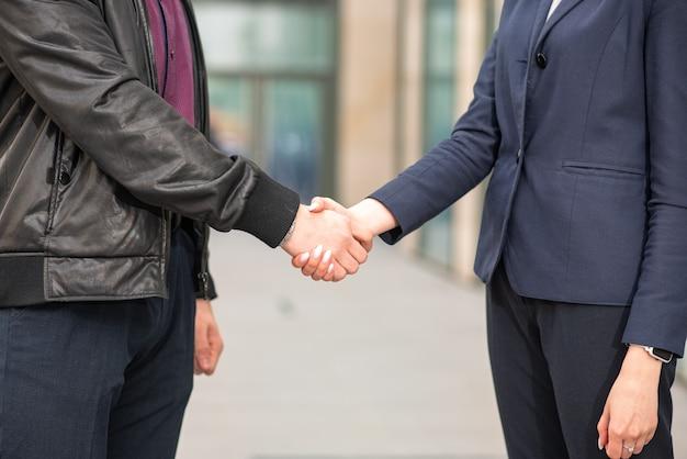 L'uomo d'affari e la donna di affari fanno una stretta di mano. etichetta aziendale.