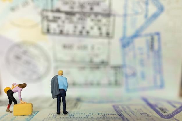 Uomo d'affari e donna d'affari figura in miniatura persone in piedi sul passaporto con timbrato immigrazione