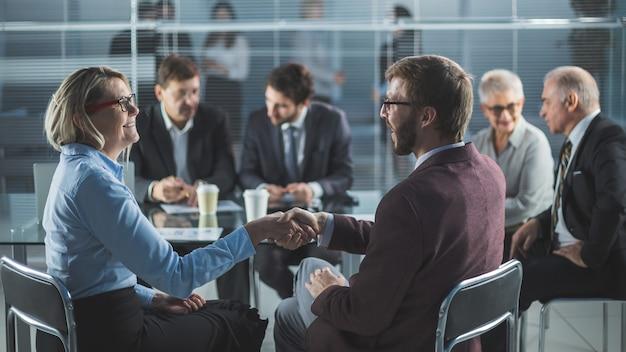 Imprenditore e imprenditrice si stringono la mano seduti al tavolo dell'ufficio. il concetto di cooperazione