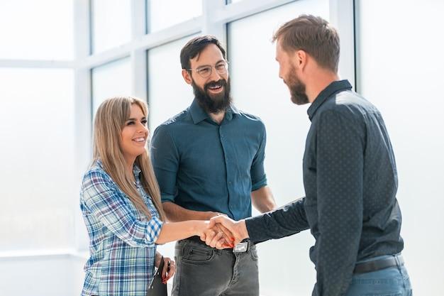 Imprenditore e imprenditrice si stringono la mano in piedi in ufficio