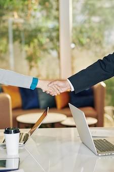 Imprenditore e imprenditrice si stringono la mano sul tavolo nella sala riunioni prima di scale di negoziati