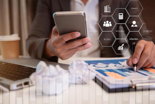 L'uomo d'affari calcola e analizza il documento grafico finanziario con lo smartphone in ufficio.