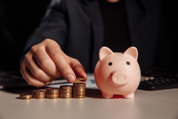 Uomo d'affari calcola il profitto, salvadanaio con una pila di monete alla scrivania. risparmio e concetto di investimento