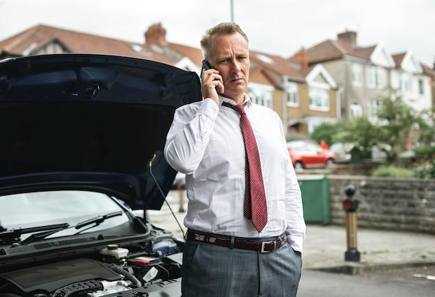 Uomo d'affari che chiede aiuto mentre la sua auto si rompe