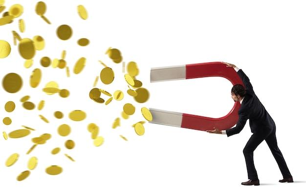 L'uomo d'affari cattura i soldi con un grande magnete. concetto di guadagnare il successo. isolato su bianco