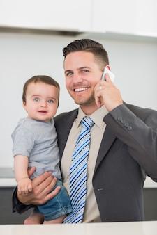 Uomo d'affari che trasportano il bambino mentre su chiamata