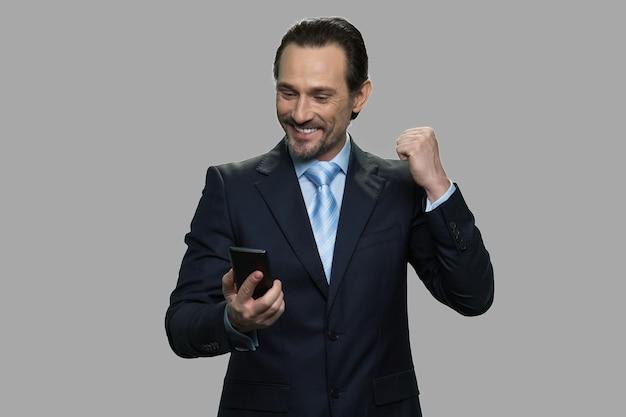 Uomo d'affari che celebra il successo durante la lettura del messaggio sullo smartphone. successo e successo aziendale.