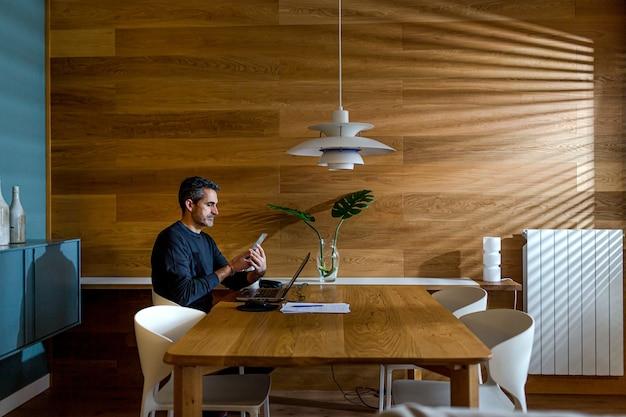 Imprenditore in chat sul suo telefono cellulare e lavorando sul suo laptop nel soggiorno di casa sua. Foto Premium