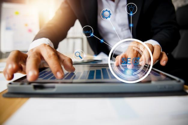 L'uomo d'affari controlla il grafico commerciale, lavora e analizza su tablet con icona finanziaria