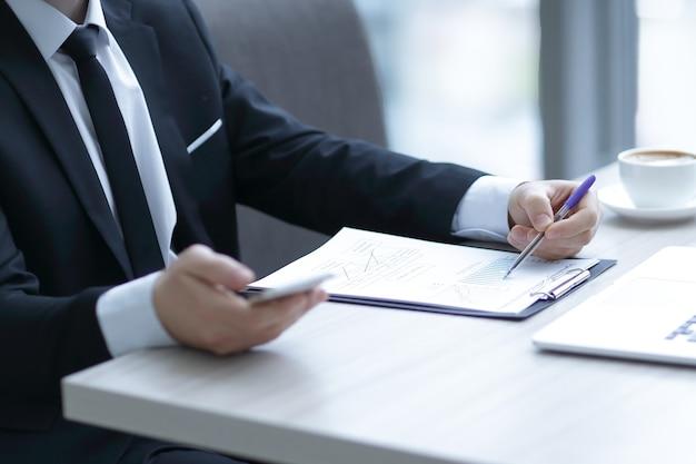 Uomo d'affari controllo rendiconto finanziario, seduto alla scrivania