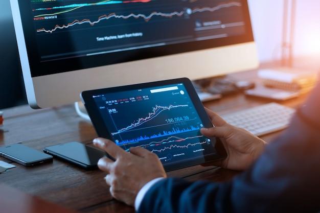 Uomo d'affari che controlla mercato azionario sulla compressa digitale