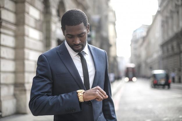 Uomo d'affari che controlla il tempo sul suo orologio mentre si cammina in strada