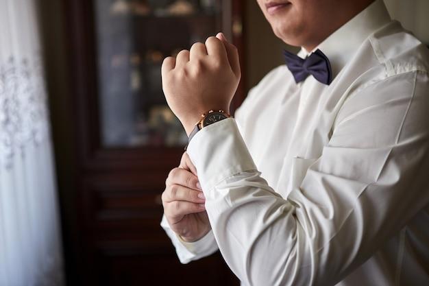 Uomo d'affari che controlla il tempo sul suo orologio da polso, uomo che mette l'orologio a portata di mano, sposo che si prepara la mattina prima della cerimonia di matrimonio. moda maschile