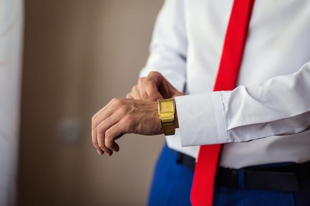 Uomo d'affari che controlla tempo sul suo orologio da polso, uomo che mette l'orologio a disposizione, sposo che si prepara al mattino prima della cerimonia di nozze