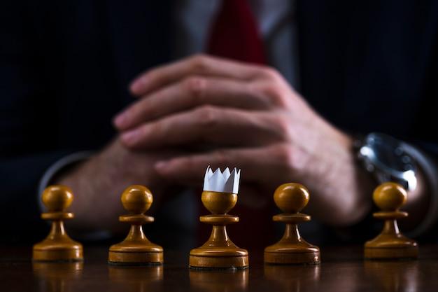 Uomo d'affari a una scacchiera davanti a una pedina con una corona di carta in testa