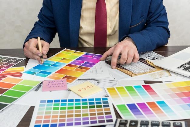 L'uomo d'affari sceglie il colore del suo appartamento moderno dopo la ristrutturazione. schizzo di casa con tavolozza di colori Foto Premium